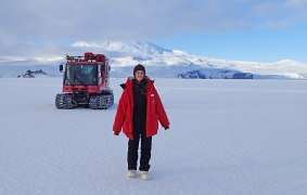 Janae on the sea ice in front of Pisten Bully and obstructed Mt. Erebus.