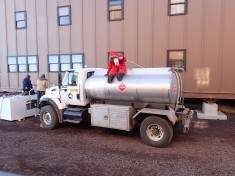 Fuel truck with a stuffed Santa on top.