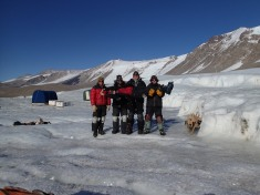 Janae in the arms of field crew at Taylor Glacier.