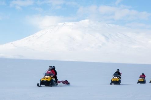 Snomos in front of Mt. Erebus. Photo credit: Lena Stevens