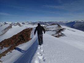 Janae and Jeremy walking on a ridge line of Mt. Newall